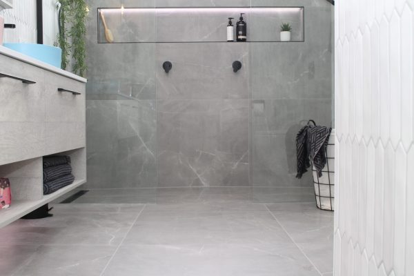 Bathroom with walk in double shower, large shower niche with lighting with large format grey floor tiles and feature wall